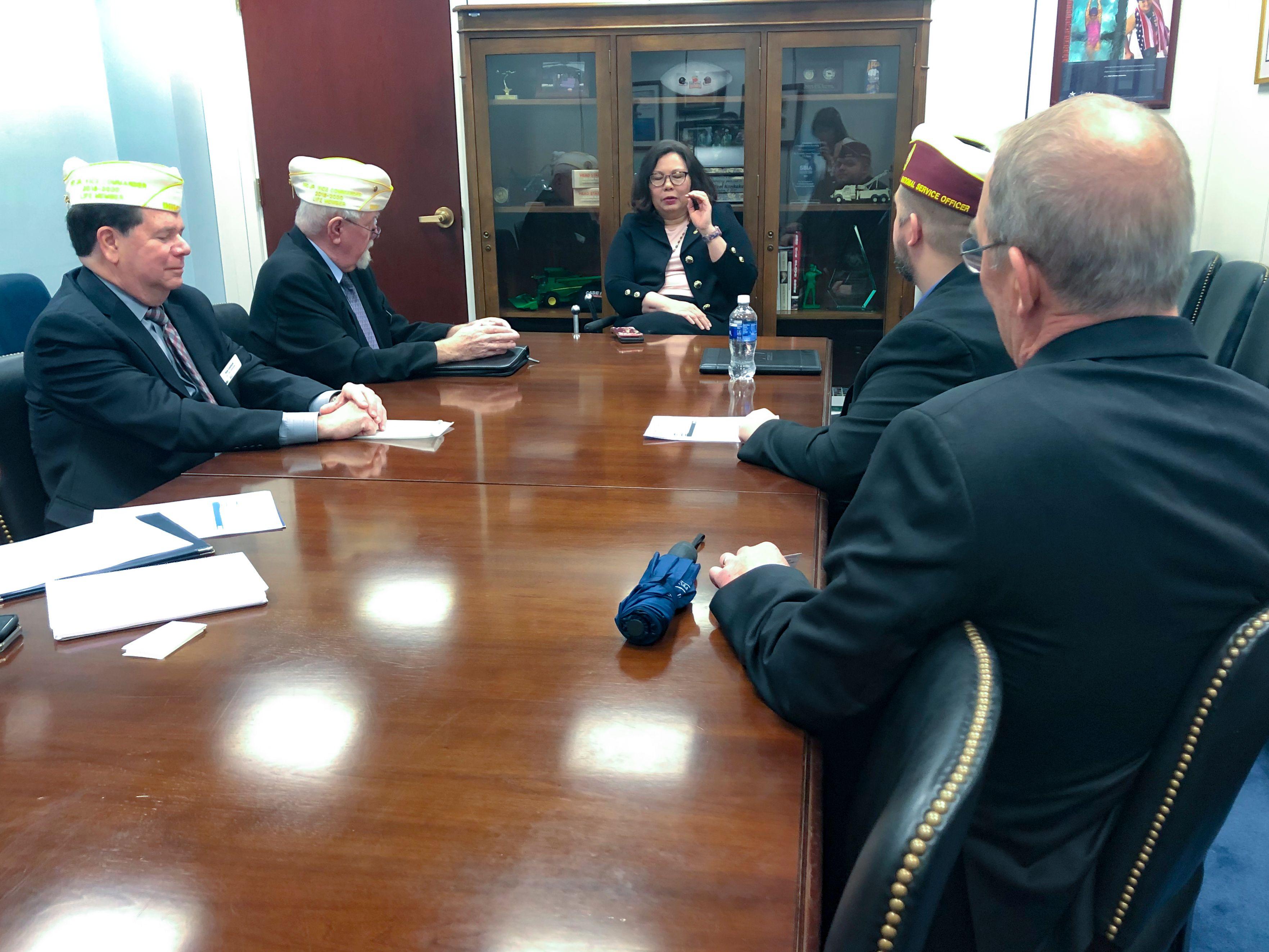 Senator meeting with DAV on legislation in a board room.