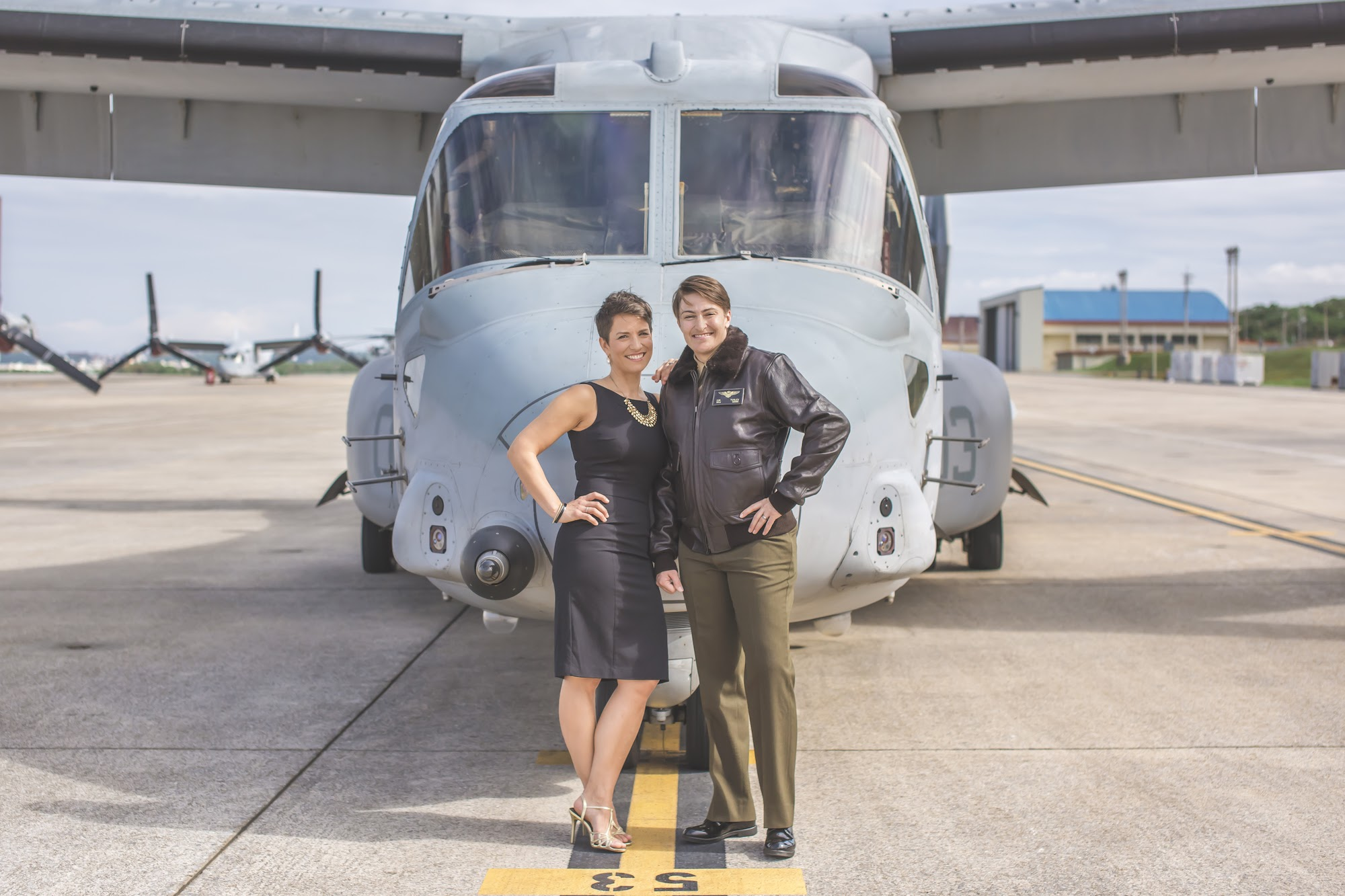 A military couple in dress and jacket, posing in front of a U.S. aircraft outside.