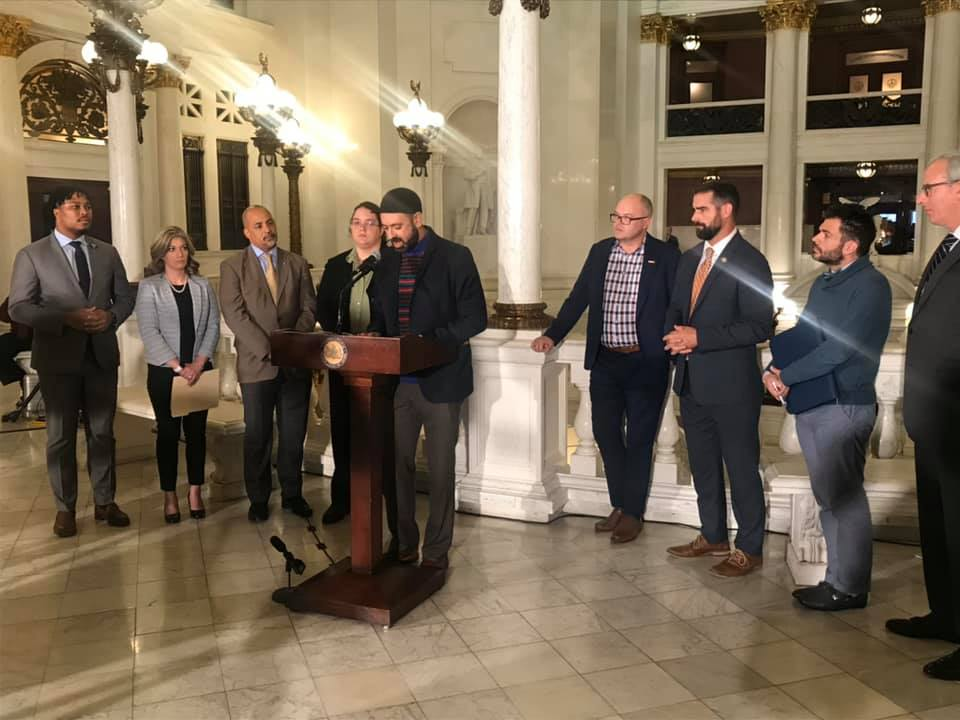 Suited Men at podium announcing the ban bill against Conversion therapy, at Pennsylvania Legislature