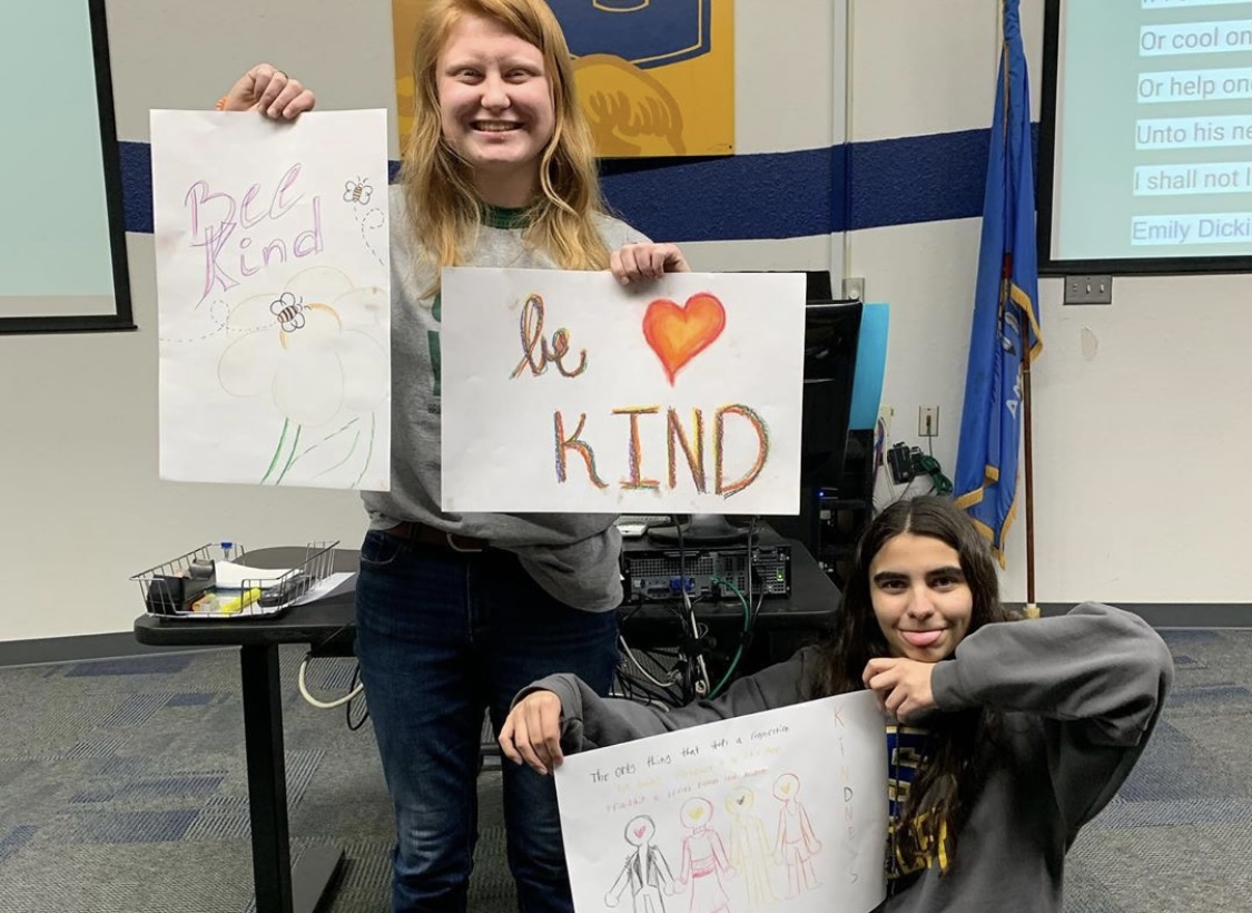 "Students in high school celebrating, holding ""Be Kind"" signs, in classroom."